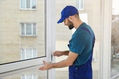Bauarbeiter, der Plastikfenster installiert lizenzfreie stockfotos