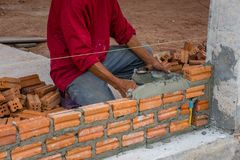 Bauarbeiter, der Ziegelsteine auf Zement für das Errichten setzt Stockfotografie