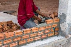 Bauarbeiter, der Ziegelsteine auf Zement für das Errichten setzt Stockfoto