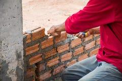 Bauarbeiter, der Ziegelsteine auf Zement für das Errichten setzt Lizenzfreie Stockfotografie