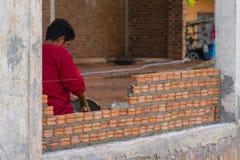 Bauarbeiter, der Ziegelsteine auf Zement für errichtendes Äußeres setzt Lizenzfreies Stockfoto