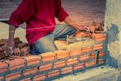 Bauarbeiter, der Ziegelsteine auf Zement für errichtendes exteri setzt Stockbild