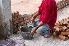 Bauarbeiter, der Ziegelsteine auf Zement für errichtendes exteri setzt stockfoto