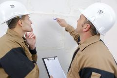 Bauarbeiter, die über Wand sprechen Stockbild