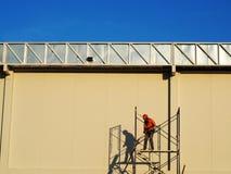 Bauarbeiter, die an Baugerüst arbeiten stockfotos