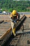 Bauarbeiter, die Betonverdichter verwenden Stockfotos