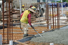 Bauarbeiter, die Betonverdichter verwenden Stockbilder