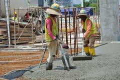 Bauarbeiter, die Betonverdichter verwenden Lizenzfreie Stockfotos