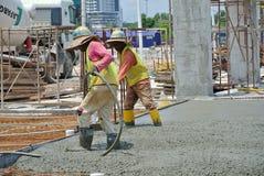 Bauarbeiter, die Betonverdichter verwenden Stockfoto