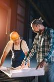 Bauarbeiter, die Blaupause überprüfend überprüfen Lizenzfreie Stockbilder