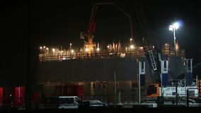 Bauarbeiter, die ein großes Gebäude während der Nachtzeit mit vielen von Löten errichten stock video footage
