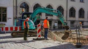 Bauarbeiter, die einen Bagger für Vorbereitung der Straße in der Fußgängerzone für Reparatur verwenden Lizenzfreie Stockbilder