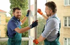 Bauarbeiter, die neues Fenster installieren stockbild