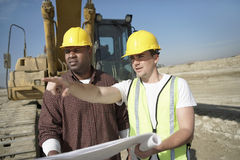 Bauarbeiter, die Plan auf Standort betrachten Lizenzfreies Stockfoto