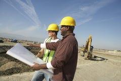 Bauarbeiter, die Plan auf Standort betrachten Lizenzfreie Stockfotos