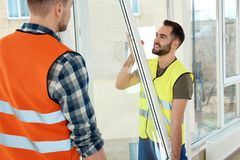 Bauarbeiter, die Plastikfenster installieren lizenzfreie stockfotografie