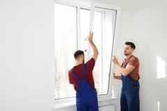 Bauarbeiter, die Plastikfenster installieren lizenzfreies stockfoto