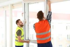Bauarbeiter, die Plastikfenster installieren stockfoto