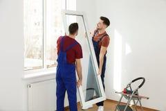 Bauarbeiter, die Plastikfenster installieren stockbilder