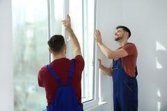 Bauarbeiter, die Plastikfenster installieren stockfotografie