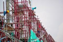 Bauarbeiter, die an rotem Baugerüst arbeiten Stockfotografie