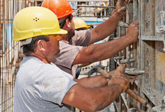 Bauarbeiter, die Verschalungfelder in Position bringen Lizenzfreies Stockbild