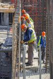 Bauarbeiter, die Verstärkungsstahlstangen binden stockbilder