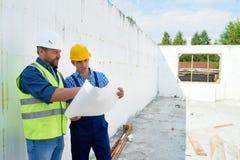 Bauarbeiter Discussing Floor Plans mit Aufsichtskraft stockfotografie
