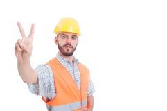 Bauarbeiter, Erbauer oder Ingenieur, die Frieden zeigen oder Sieger Lizenzfreie Stockfotos