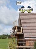Bauarbeiter gehockt auf einem Dach Stockbild