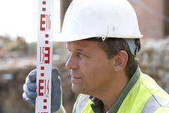 Bauarbeiter-Holding-Maß Lizenzfreies Stockfoto