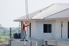 Bauarbeiter installieren Kranhaken an der Vorgußbetonmauer, Vorgußhaus stockfoto