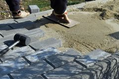 Bauarbeiter legen Betondeckestein für Fußwegenarbeit an der Baustelle Pflastersteinarbeitskraft setzt sich lizenzfreies stockfoto