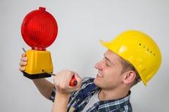 Bauarbeiter mit einer roten Baustandortlampe Lizenzfreies Stockfoto