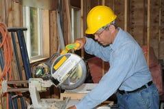 Bauarbeiter mit einer Säge Stockbild