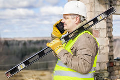Bauarbeiter mit Niveau und Handy Lizenzfreie Stockfotografie