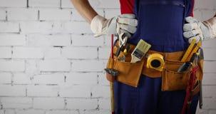 Bauarbeiter mit Werkzeuggurtstellung auf weißem Backsteinmauerhintergrund stock video footage