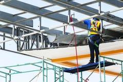 Bauarbeiter setzte an Schutzausrüstungstat auf das scaff stockfotos