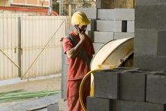 Bauarbeiter spricht am horizontalen Telefon - Stockfotografie