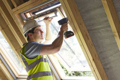 Bauarbeiter Using Drill To installieren Fenster Stockfotos
