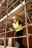 Bauarbeiter, Vorarbeiter oder Architekt auf Baugerüst an der Baustelle mit dem Klemmbrett, lächelnd in Richtung zur Kamera lizenzfreie stockfotografie