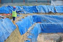 Bauarbeiter, welche die chemische Behandlung der Antitermite zur Stapelkappe sprühen Lizenzfreie Stockfotos
