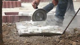 Bauarbeiterausschnitt-Pflasterungsstein mit einem Winkelschleifer 4K mit Audio stock footage