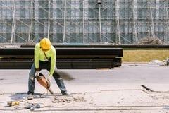 Bauarbeiterelektrische bohrmaschine, die herein konkreten Boden bohrt Lizenzfreies Stockbild