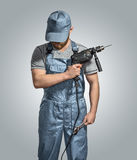 Bauarbeitererbauer mit Bohrgerät und Schlüssel auf dem lokalisierten Hintergrund Lizenzfreie Stockfotos