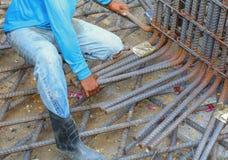 Bauarbeiterhand, die Verstärkungsmasche an der Baustelle installierend arbeitet Stockbild