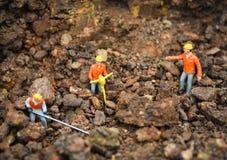 Bauarbeiterkonzept/-figürchen, die grabenden Grundboden mit dem Teamingenieurschauen bearbeiten lizenzfreies stockfoto
