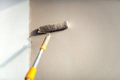 Bauarbeitermalereiwände unter Verwendung der Farbenrolle stockbild