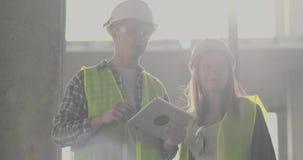 Bauarbeitermann und Architektenfrau in einem Sturzhelm, besprechen den Plan des Baus des Hauses, sich sagen stock footage