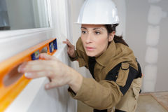 Bauarbeitnehmerin, die waagerecht ausgerichtetes Werkzeug auf Hausmauer verwendet Lizenzfreie Stockfotografie